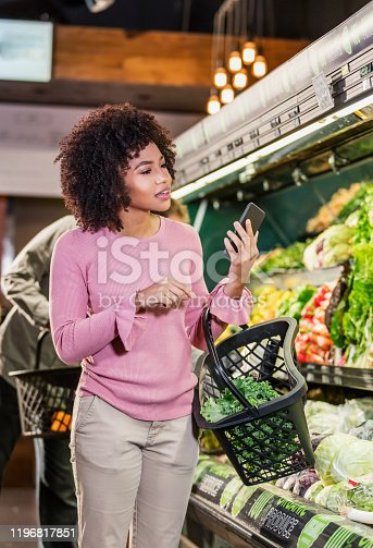 istock Young African-American woman shopping in grocery store 1196817851