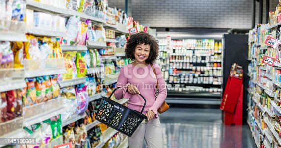 istock Young African-American woman shopping in supermarket 1145100664