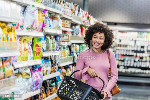 istock Young African-American woman shopping in supermarket 1145101341