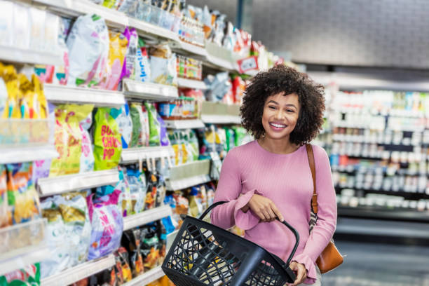 Young African-American woman shopping in supermarket A young African-American woman in her 20s shopping in a grocery store, carrying a shopping basket. She is standing in the snack aisle, smiling at the camera. snack aisle stock pictures, royalty-free photos & images
