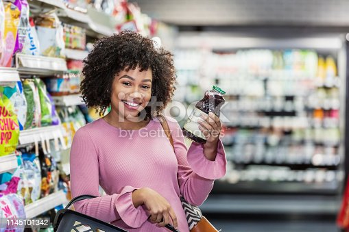 istock Young African-American woman shopping in supermarket 1145101342