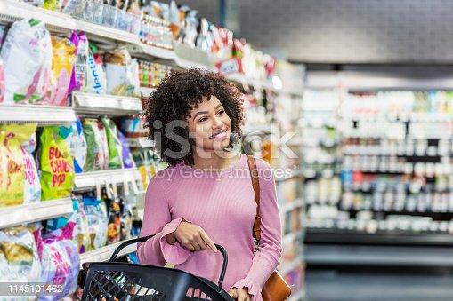 istock Young African-American woman shopping in supermarket 1145101462