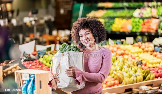 istock Young African-American woman shopping in supermarket 1145101586