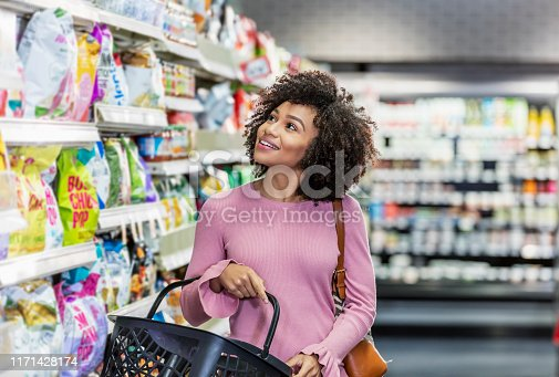 istock Young African-American woman shopping in supermarket 1171428174