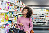 A young African-American woman in her 20s shopping in a grocery store, carrying a shopping basket. She is standing in the snack aisle, smiling and looking around.
