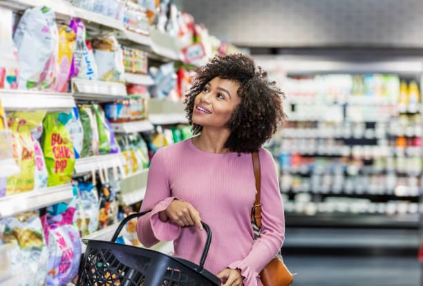 Young African-American woman shopping in supermarket A young African-American woman in her 20s shopping in a grocery store, carrying a shopping basket. She is standing in the snack aisle, smiling and looking around. aisle stock pictures, royalty-free photos & images