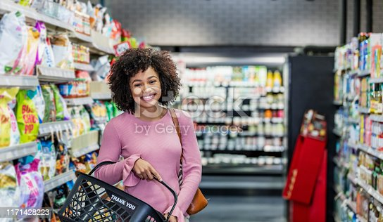 istock Young African-American woman shopping in supermarket 1171428223