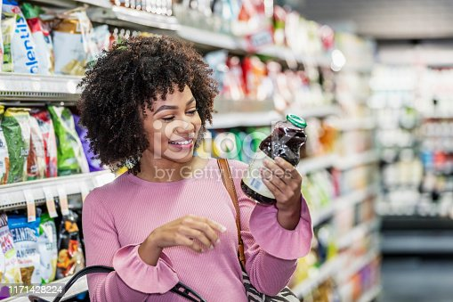 istock Young African-American woman shopping in supermarket 1171428224