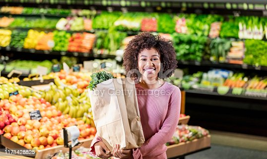 istock Young African-American woman shopping in supermarket 1171428825