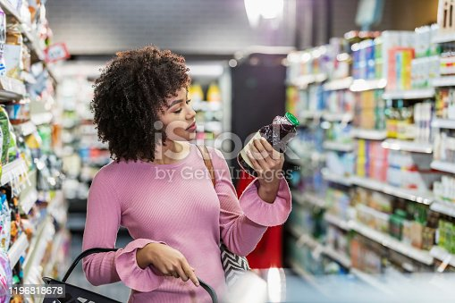 istock Young African-American woman shopping in supermarket 1196818678