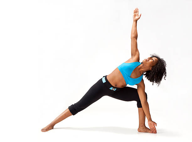 young African-American woman standing in yoga warrior pose stock photo