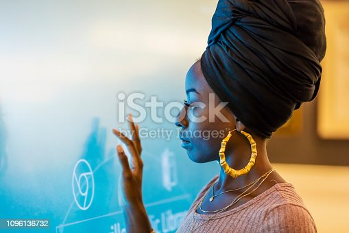 A young African-American woman in her 20s wearing a turban and large earrings, touching a giant interactive display screen.