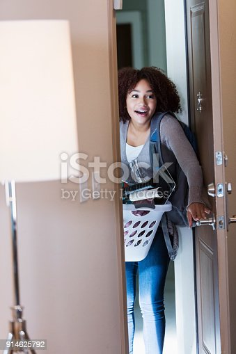 istock Young African-American woman walking through door 914625792