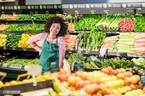 istock Young African-American woman working in grocery store 1145100208