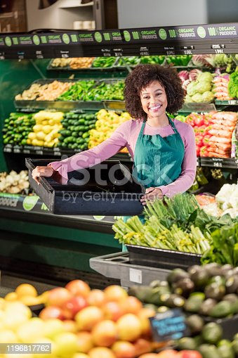 istock Young African-American woman working in grocery store 1196817762