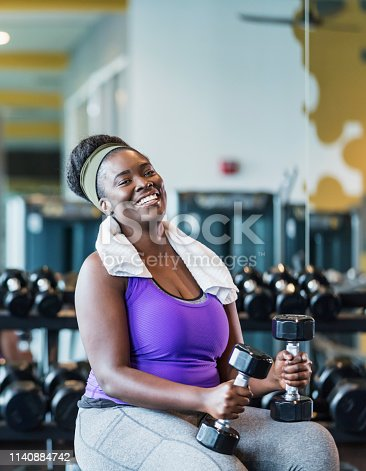 A young African-American woman in her 20s working out at the gym, sitting on a weight bench holding a dumbbell in each hand, smiling at the camera.