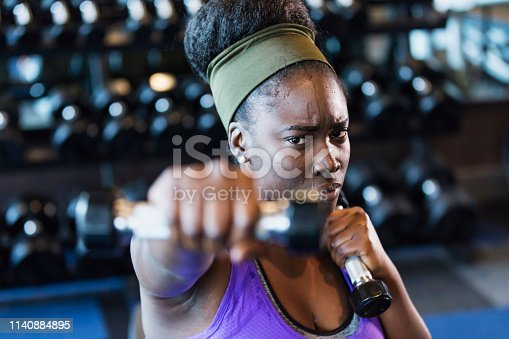 Close-up of a young African-American woman in her 20s working out at the gym. She is holding a dumbbell in each hand, extending one of them toward the camera, with a confident and determined expression.