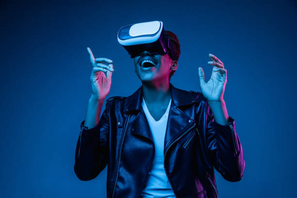 Young african-american woman's using VR-glasses in neon light stock photo