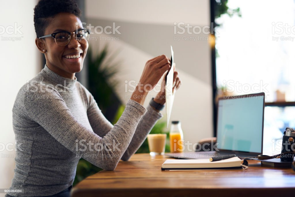 Young afro american international student in trendy glasses happy to receive letter from best friend being far away from home practicing as trainee in trading company working with database via laptop stock photo