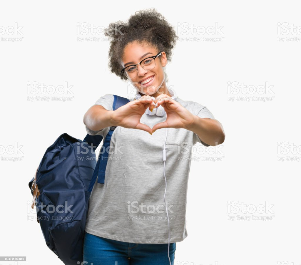 Young afro american student woman wearing headphones and backpack over isolated background smiling in love showing heart symbol and shape with hands. Romantic concept. stock photo
