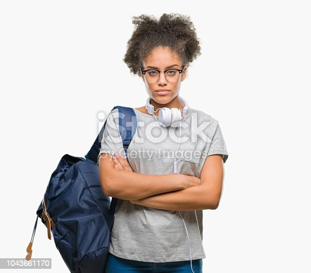 istock Young afro american student woman wearing headphones and backpack over isolated background skeptic and nervous, disapproving expression on face with crossed arms. Negative person. 1043661170