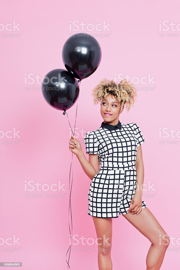 Young afro American woman holding two black balloons Summer portrait of afro american young woman wearing grid check playsuit, standing against pink background, holding two black balloons 2016 Stock Photo