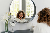 Natural beauty concept. Happy young afro american woman sitting in bathrobe near mirror at bathroom, smiling wide, enjoying morning routine, rejuvenation, face massage and spa procedure at home
