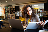 istock Young afro american woman sitting at table with books and laptop for finding information 1266628951