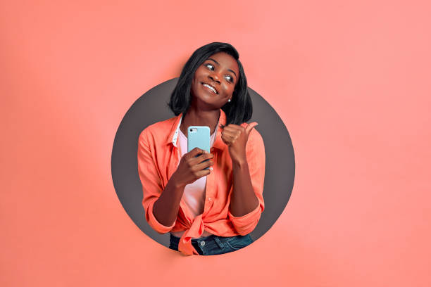 Young afro american woman texting using smartphone over isolated background pointing and showing with thumb up to the side with happy face smiling. Copy space. stock photo