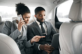 Young afro business couple working on back seat of car, going to office