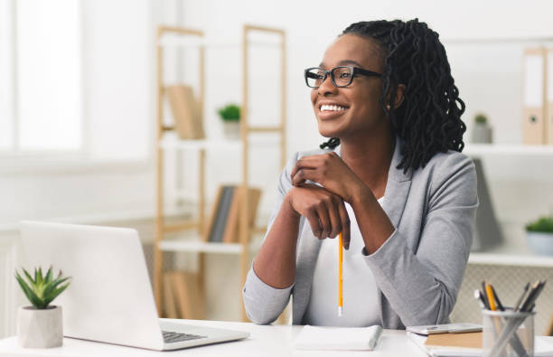 Young Afro Business Lady Smiling Sitting In Modern Office Business Career Concept. Afro Businesswoman Smiling Sitting In Modern Office. Copy Space business laptop stock pictures, royalty-free photos & images