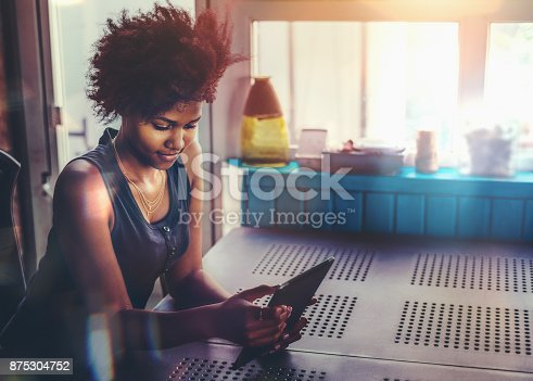 istock Young Afro female at the table with tablet pc 875304752