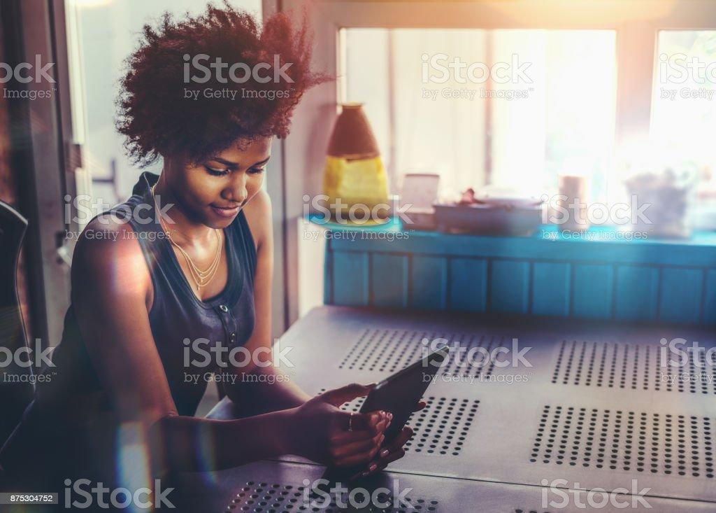 Junge Afro Frau am Tisch mit TabletPC – Foto
