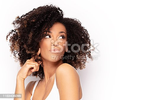 Young fashionable afro girl posing. White studio background.