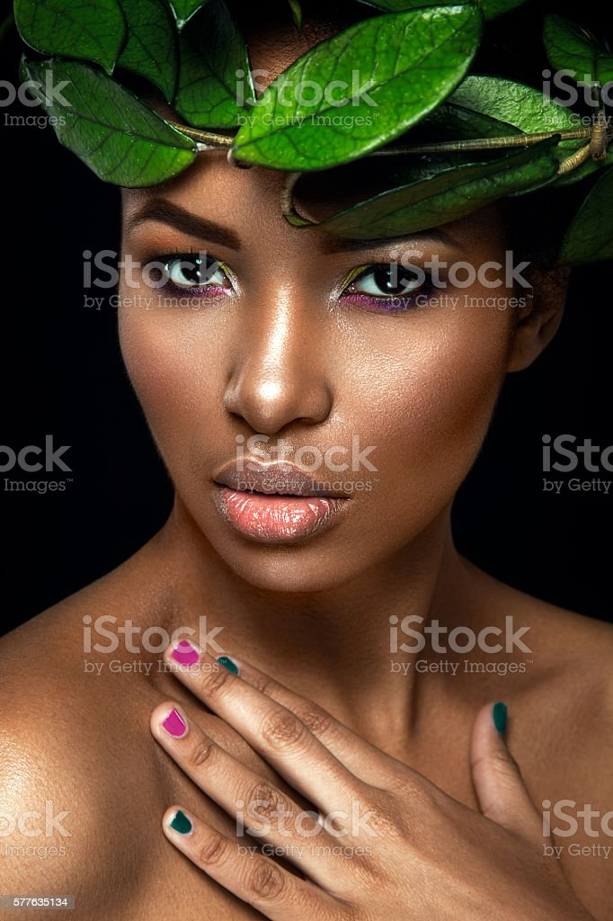 Young afro girl posing with green leaves stock photo