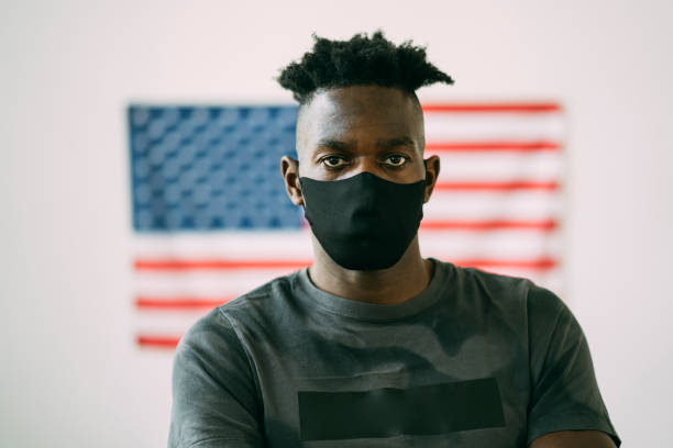 Young afro man with a face protection Portrait of an afro-American man with a face protection standing in front of the American flag civil rights stock pictures, royalty-free photos & images