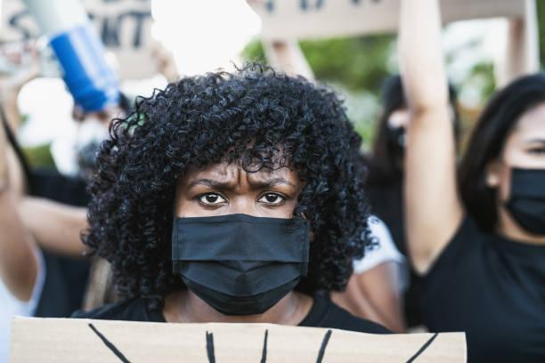 joven activista afro afro protesta contra el racismo y la lucha por la igualdad - las vidas negras importan manifestaciones en la calle por la justicia y la igualdad de derechos - civil rights fotografías e imágenes de stock