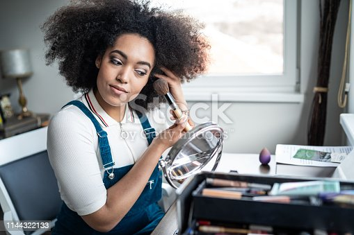 Young afro woman applying makeup at home