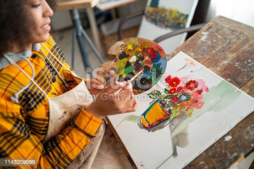 istock Young afro woman drawing 1143209599