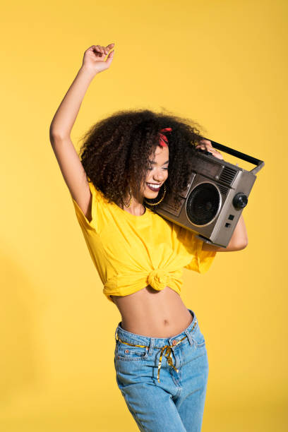 Young afro woman holding boombox and dancing stock photo