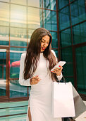 istock Young afro woman in white dress with paper shopping bags and use smartphone outdoors against the background of a business building 1211168077