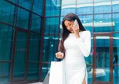 istock Young afro woman in white dress with paper shopping bags talking on the phone outdoors against the background of a business building 1170150593