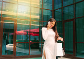 istock Young afro woman in white dress with paper shopping bags talking on the phone outdoors against the background of a business building 1211168126