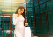 istock Young afro woman in white dress with paper shopping bags talking on the phone outdoors against the background of a business building 1211168581