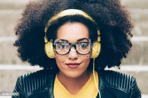 istock Young afro woman listening music 516216692