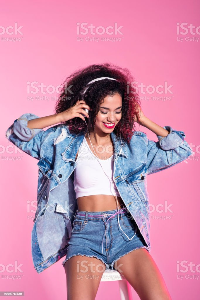 Young afro woman listening to music стоковое фото