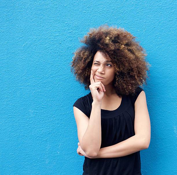 giovane donna pensando afro - mano sul mento foto e immagini stock