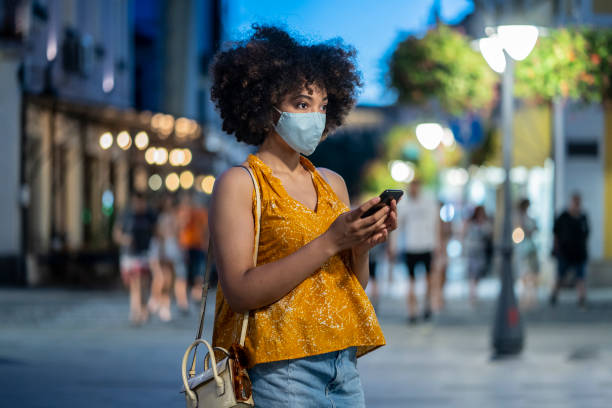 young afro woman using her mobile phone on the street while awning of a friend - afro latino mask imagens e fotografias de stock
