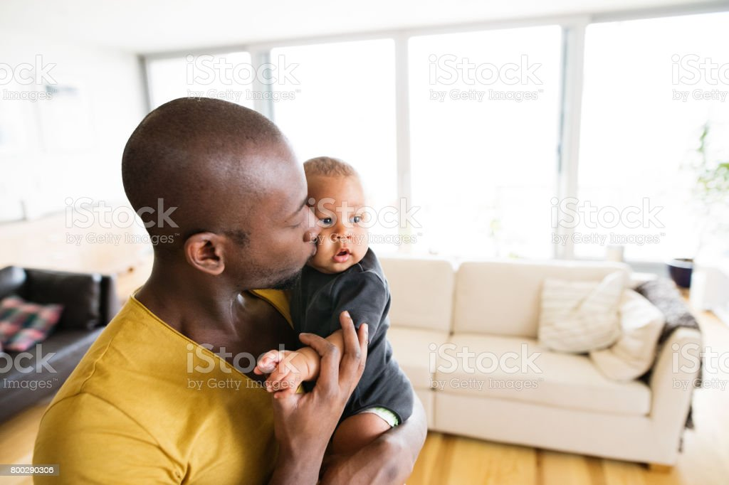 Young afro-american father holding his baby son in the arms stock photo
