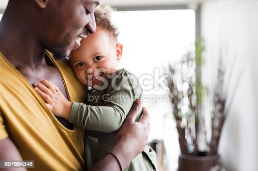 istock Young afro-american father with his little daughter at home. 697884348